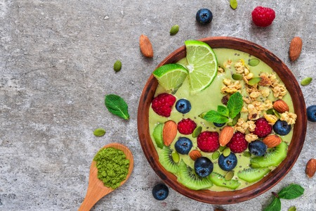 matcha green tea smoothie bowl with fresh fruits, berries, nuts, seeds and granola for healthybvegetarian diet breakfast. top view with copy space. flat lay Imagens