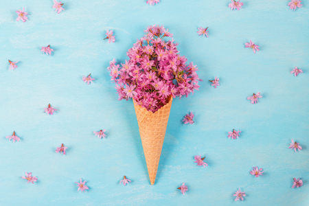Ice cream of pink blossom cherry flowers in waffle cone on pastel colored blue background with buds. flat lay. top view. wedding or holiday background