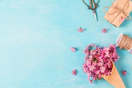 wedding or holiday background with ice cream cone with cherry blossom flowers and gift box on blue wooden background. flat lay. top view with copy space Reklamní fotografie