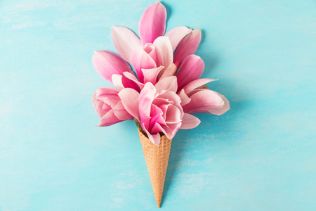 Ice cream of pink magnolia flowers in waffle cone on pastel colored blue background. flat lay. top view. wedding or holiday background Stock Photo
