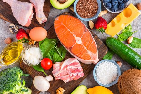 Keto diet concept. Ketogenic diet food. Balanced low carb food background. Vegetables, fish, meat, cheese, nuts, seeds on wooden background. top view Imagens - 126269569