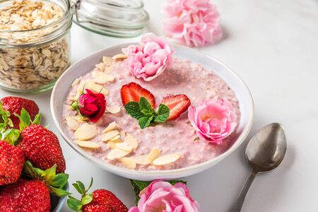 romantic healthy breakfast. overnight strawberry oats with fresh berries, almonds and mint in a bowl with rose flowers and spoon on white marble table. close up