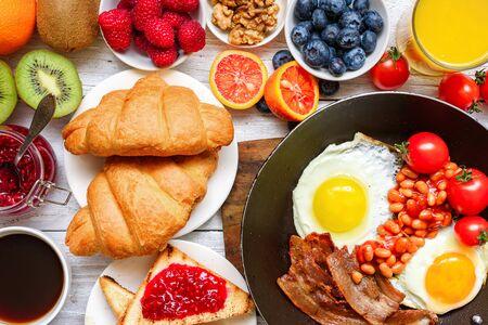 Desayuno buffet continental completo con huevos fritos, tocino, frutas, tostadas, croissants, frutos del bosque, café y jugo de naranja. vista superior