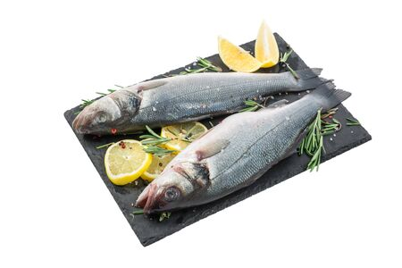 Fresh fish seabass and ingredients for cooking, lemon, pepper and rosemary on black slate isolated on white background. close up