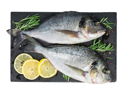 Fresh fish dorado or sea bream and ingredients for cooking, lemon, pepper and rosemary on black slate isolated on white background. top view Reklamní fotografie