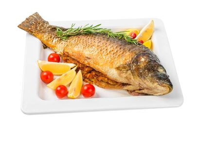 whole fish carp baked in a dish with lemon, cherry tomatoes and rosemary isolated on white background. close up