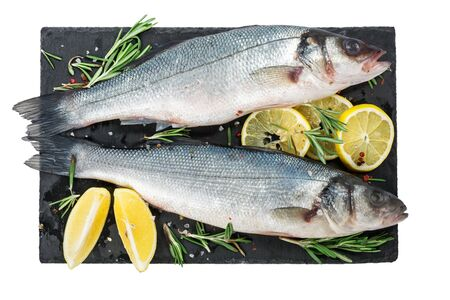 Fresh fish seabass and ingredients for cooking, lemon, pepper and rosemary on black slate isolated on white background. top view