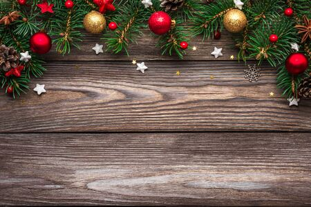 Christmas and Happy New Year background. Fir tree branches and red with gold holiday decorations on rustic wooden table. top view. flat lay with copy space