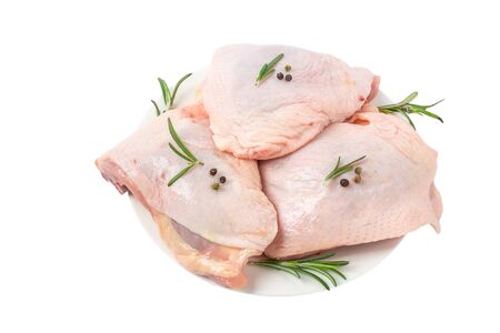 Raw chicken hip meat in a plate with herbs and spices isolated on white background. close up