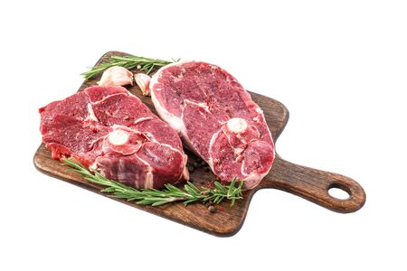 Raw lamb steak on a bone on wooden cutting board with herbs and spices isolated on white background. close up