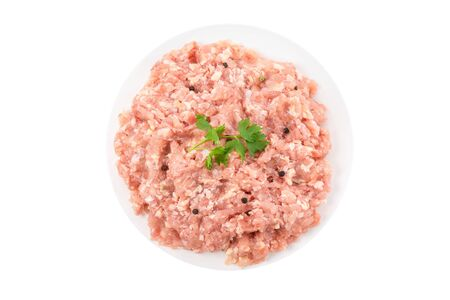 Raw chicken minced meat in a plate with herbs and spices isolated on white background. top view