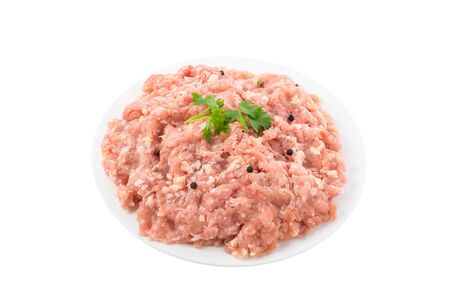 Raw chicken minced meat in a plate with herbs and spices isolated on white background. close up