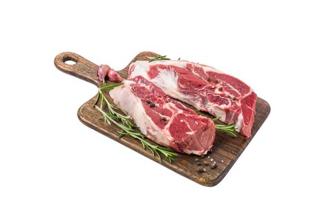 Raw lamb meat on a bone on wooden cutting board with herbs and spices isolated on white background. close up