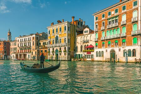 Venetian gondolier punting gondola through Grand Canal along colorful building facades in Venice, Italy