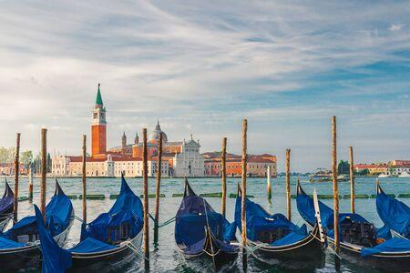 Gondolas moored by Saint Mark square with San Giorgio di Maggiore church on background in Venice, Italy during sunrise Stok Fotoğraf