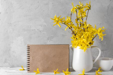 Still life with a beautiful spring yellow forsythia flowers, coffee cup and blank greeting card on concrete background. mock up. holiday or wedding concept