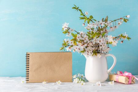 Still life with a beautiful spring cherry blossom flowers, gift box and blank paper notebook on white wooden table. mock up. holiday or wedding background