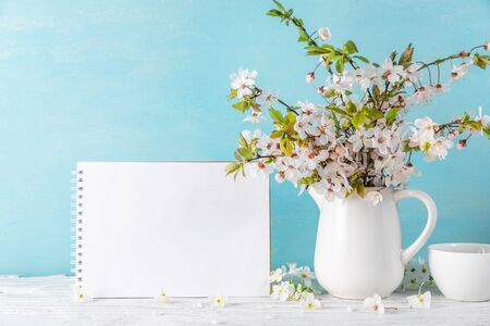 Still life with a beautiful spring cherry blossom flowers, coffee cup and blank greeting card on blue background. mock up. holiday or wedding concept