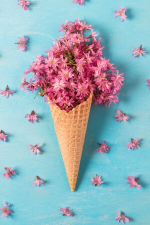 Ice cream cone with spring blossom pink cherry or sakura flowers on blue background. Minimal spring concept. Flat lay. top view. vertical orientation Stok Fotoğraf
