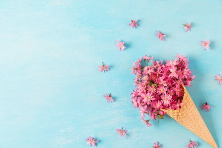 Ice cream cone with spring blossom pink cherry or sakura flowers on blue background with copy space. Minimal spring concept. Flat lay. top view