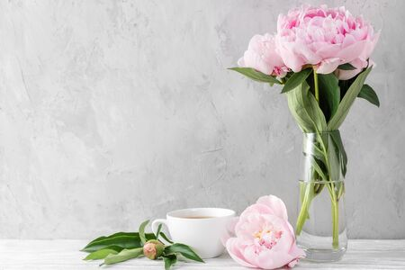 Festive pink peony flowers bouquet with coffee cup on white table with copy space. still life. womens day or wedding background