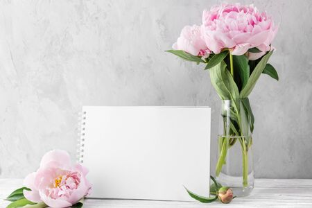 pink peony flowers bouquet with blank greeting card or wedding invitation on white table with copy space. mock up. still life. womens day or wedding concept. festive background Stok Fotoğraf