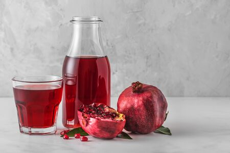Pomegranate juice in a bottle with glass of juice and fresh pomegranate fruits on marble table. Healthy drink concept