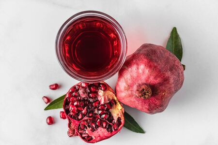 Glass of pomegranate juice with fresh pomegranate fruits on marble table. Top view. Healthy drink concept Stok Fotoğraf