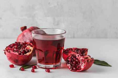 Glass of pomegranate juice with fresh pomegranate fruits on marble table. Healthy drink concept