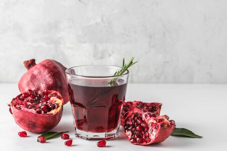 Glass of pomegranate juice with fresh pomegranate fruits and rosemary on marble table. Healthy drink concept