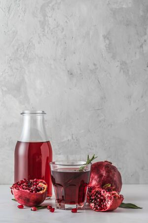 Pomegranate juice with fresh pomegranate fruits and rosemary on marble table. Vertical orientation. Healthy drink concept