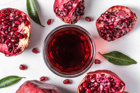 Top view of pomegranate juice in a glass with fresh pomegranate fruits on marble table. Top view. Healthy drink concept Stok Fotoğraf