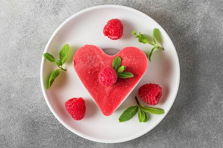 Valentines day dessert. heart shaped raw vegan red cake with raspberries and mint in a plate. healthy delicious food. top view. love concept Stok Fotoğraf