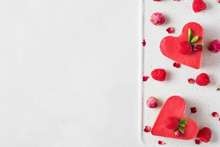 heart shaped red raw vegan cakes with fresh raspberries, mint and dried flowers. Valentines day dessert. healthy delicious food. top view with copy space. love concept