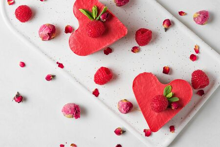 Valentines day dessert. heart shaped raw vegan red cakes with raspberries, dried rose flowers and mint. healthy delicious food. top view. love concept Stok Fotoğraf