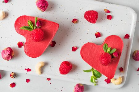 raw vegan heart shaped cakes or cheesecakes with fresh raspberries, mint and dried flowers. Valentines day dessert. healthy food concept. top view
