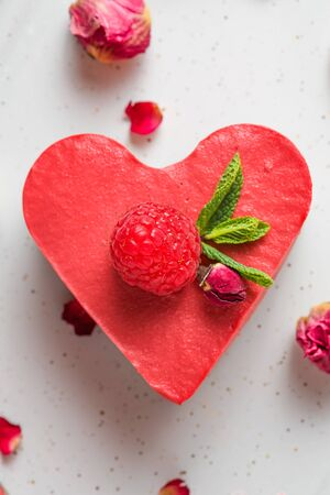 heart shaped raw vegan cake or cheesecake with fresh raspberries, mint and dried flowers. Valentines day dessert. healthy delicious food. top view. Vertical orientation
