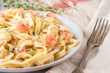 Italian pasta fettuccine or tagliatelle with shrimps in a creamy sauce with parmesan cheese and thyme in a plate on white marble table. close up Stok Fotoğraf