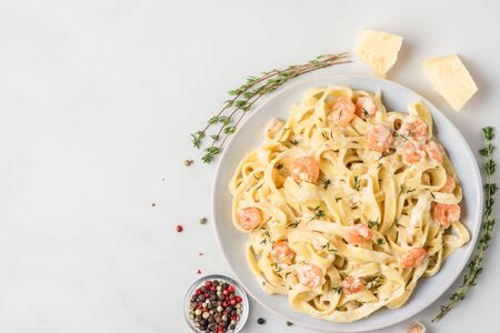 Italian pasta fettuccine with shrimps in a creamy sauce with parmesan cheese and thyme in a plate on white marble table. top view with copy space