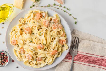 Italian pasta fettuccine or tagliatelle with shrimps in a creamy sauce with parmesan cheese and thyme in a plate on white marble table. top view