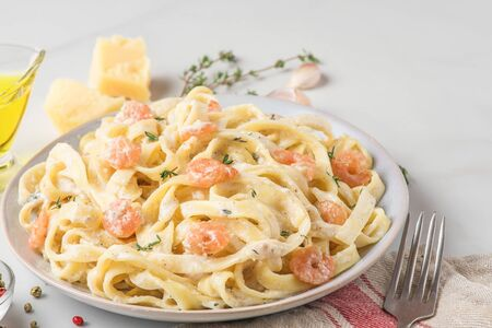 Italian pasta fettuccine with shrimps in a creamy sauce with parmesan cheese and thyme in a plate on white marble table. close up
