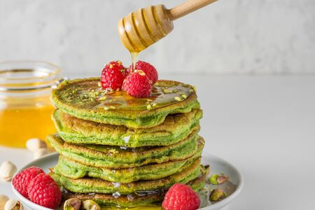 Matcha tea green pancakes. Pile of homemade pancakes with fresh raspberries, pistachios and flowing honey. healthy breakfast dessert