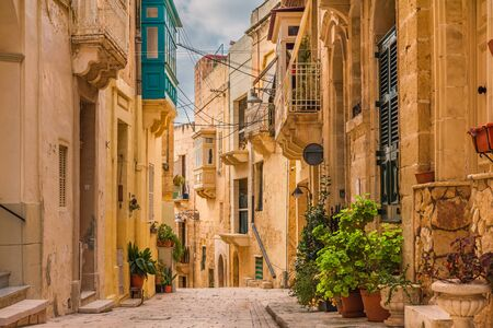 Old medieval street with yellow buildings, beautiful balconies and flower pots in Birgu, Valletta, Malta with nobody Stok Fotoğraf