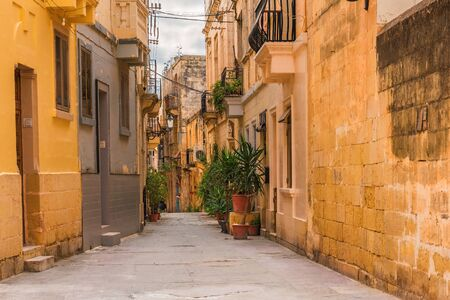 Old medieval street with yellow buildings and flower pots in Birgu, Valletta, Malta with nobody Stok Fotoğraf