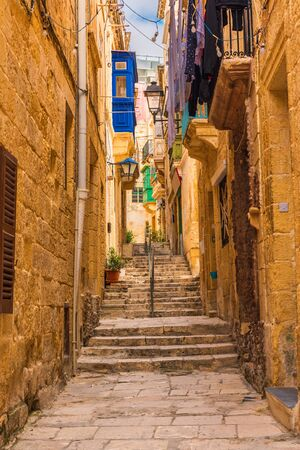 Old narrow medieval street with yellow buildings with colorful balconies in town Singlea, Valletta, Malta with nobody. vertical orientation