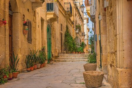 Old narrow medieval street with yellow buildings and flower pots in Valletta, Malta with nobody