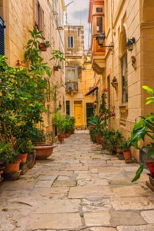 Valletta, Malta. Old medieval empty street with yellow buildings and flower pots in Singlea. Vertical orientation