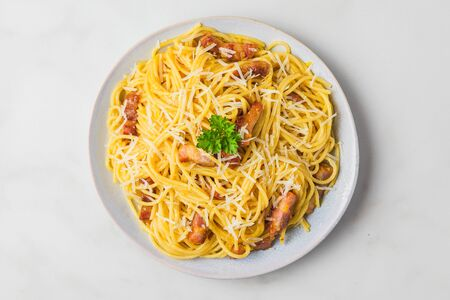 Carbonara pasta, spaghetti with guanciale, egg, hard parmesan cheese and parsley. Traditional italian cuisine. top view Stok Fotoğraf