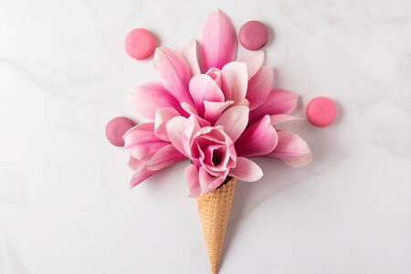Creative layout made with pink magnolia flowers in waffle cone with macaroons on white marble background. Flat lay. top view. wedding or womans day composition. spring concept Stok Fotoğraf
