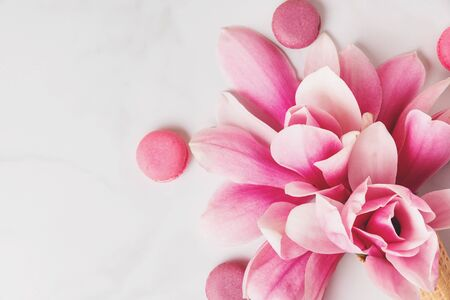 Beautiful spring pink magnolia flowers with macaroons on white table with copy space for your text. top view. flat lay. wedding or womens day background